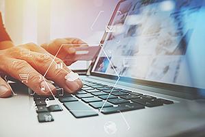 Eine Hand liegt auf der Tastatur eines Laptops